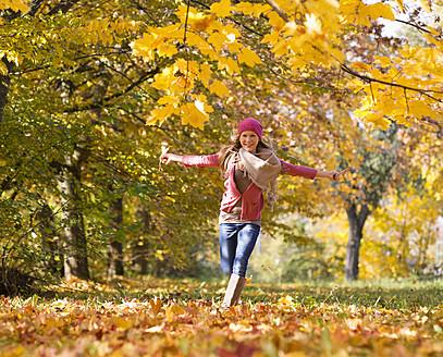 Austria, Teenage girl running on autumn leaf - WWF002163