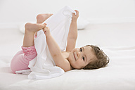 Baby girl lying on back and holding toes, smiling - SMOF000459