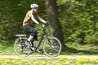 Germany, Bavaria, Munich, Mature man riding electric bicycle - DSF000231