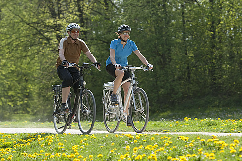 Germany, Bavaria, Munich, Man and woman riding electric bicycle - DSF000234