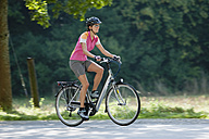 Germany, Bavaria, Munich, Mid adult woman riding electric bicycle - DSF000237