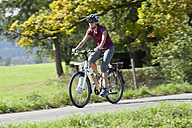 Germany, Bavaria, Mid adult woman riding electric bicycle - DSF000240