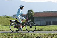 Germany, Bavaria, Mid adult woman riding electric bicycle - DSF000243