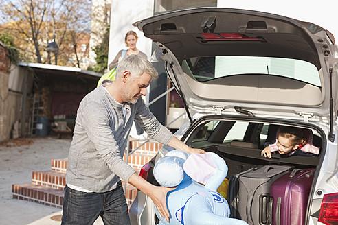 Germany, Leipzig, Father loading luggage into car - WESTF018429