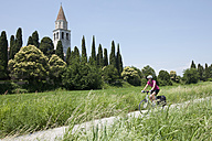 Italy, Aquileia, Mid adult woman riding bicycle - DSF000278