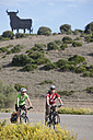 Spain, Andalusia, Man and woman riding bicycle with bull statue in background - DSF000294