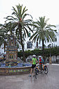 Spain, Andalusia, Vejer , Man and woman with bicycle standing by fountain - DS000292