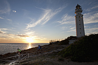 Spain, Andalusia, Man and woman riding bicycle by light house at sunset - DSF000275