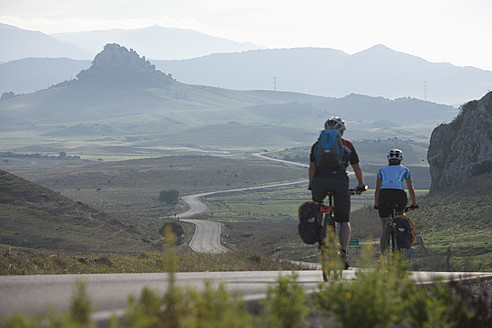 Spain, Andalusia,  Man and woman cycling through country road - DSF000288