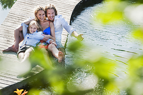Austria, Salzburg County, Family sitting on bridge over natural pool - HHF003989