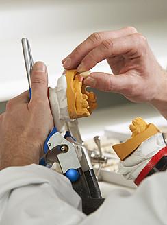 Dentist preparing dentures in dental laboratory - WWF002128