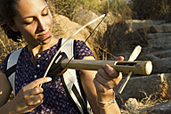 India, Goa, Young woman playing handmade wooden instrument - MBEF000264