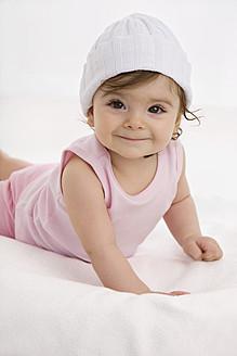 Baby girl lying on baby blanket, smiling - SMOF000504