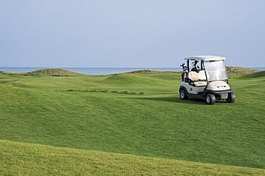 Turkey, Antalya, Golf cart on meadow at golf course - GNF001207