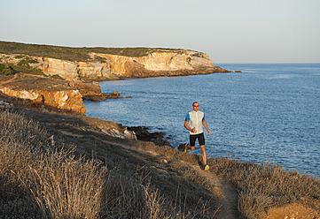 Portugal,Algarve,  Mature man jogging by coast - MIRF000369