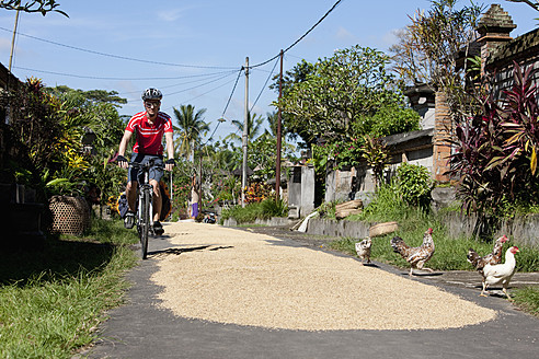 Indonesia, Bali, Tegalalang, Man cycling through street - DSF000214