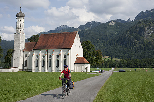 Germany, Bavaria, Fuessen, Mature man riding bicycle with church in background - DSF000283
