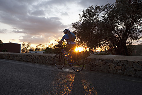 Spain, Ibiza, Mid adult woman riding bicycle - DSF000306