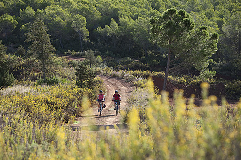Spain, Ibiza, Mature man and mid adult woman riding bicycle - DSF000308