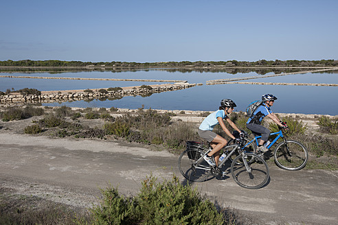 Spain, Formentera, Mature man and mid adult woman riding bicycle - DSF000318