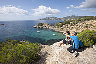 Spain, Ibiza, Porroig, Mature man and mid adult woman looking at view - DSF000324