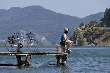 Turkey, Dylan Delta, Mid adult woman sitting on jetty with bicycle - DSF000363