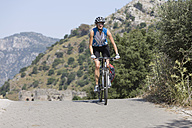 Turkey, Lycian Coast,  Mid adult woman riding bicycle - DSF000366