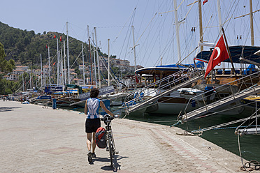 Turkey, Fethiye, Mid adult woman walking at harbour with bicycle - DS000377