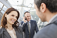 Germany, Leipzig, Business people smiling, businessman with cell phone in background - WESTF018450