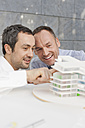 Germany, Leipzig, Business people discussing about architectural model - WESTF018495