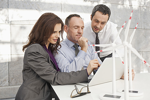 Germany, Leipzig, Business people using laptop and discussing about wind power model - WESTF018522