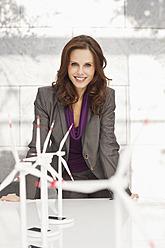 Germany, Leipzig, Businesswoman with wind power model - WESTF018528