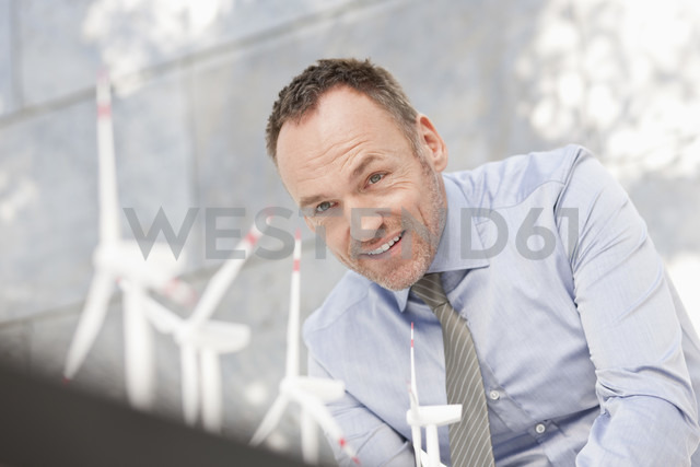 Germany, Leipzig, Businessman with wind power model - WESTF018537