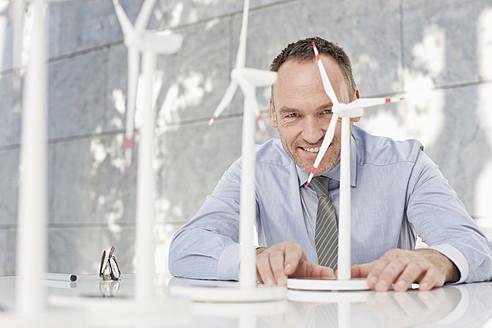 Germany, Leipzig, Businessman with wind power model - WESTF018540