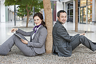 Germany, Leipzig, Business people sitting at tree with digital tablet and cell phone - WESTF018570