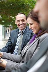 Germany, Leipzig, Business people sitting on bench, smiling - WESTF018585