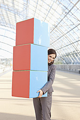 Germany, Leipzig, Businesswoman with cubes, smiling, portrait - WESTF018600