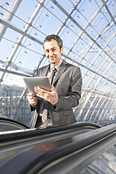 Germany, Leipzig, Businessman using digital tablet on escalator, portrait - WESTF018636