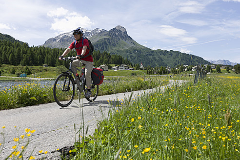 Switzerland, Mature man cycling through country road by Lake Sils - DSF000391