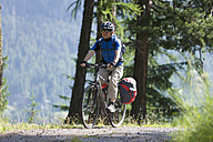 Switzerland, Mature man cycling on dirt track - DSF000397