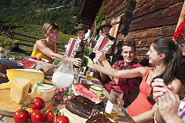 Austria, Salzburg County, Men and women sitting at alpine hut, listening to musicians - HHF004030