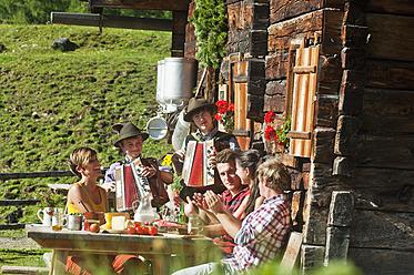Austria, Salzburg County, Men and women sitting at alpine hut, listening to musicians - HHF004031
