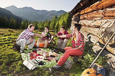 Austria, Salzburg, Men and women having picnic near alpine hut at sunset - HHF004038