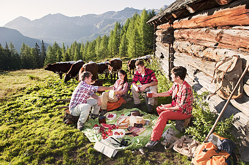 Austria, Salzburg County, Men and women having picnic near alpine hut at sunset - HHF004035