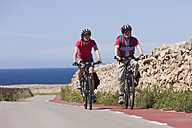 Spain, Menorca, Punta Nati, Man and woman cycling on road - DSF000523