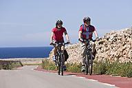 Spain, Menorca, Punta Nati, Man and woman cycling on road - DSF000523