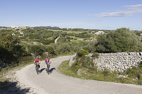 Spain, Menorca, Man and woman cycling on country road - DSF000508