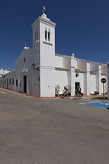 Spain, Menorca, Man and woman cycling by church in Fornells - DSF000514