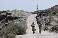 Spain, Menorca, Man and woman cycling, Cap de Favaritx in background - DSF000517