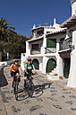 Spain, Minorca, Binibeca, Man and woman cycling through promenade - DSF000498